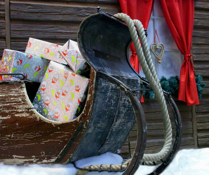 old wooden sleigh loaded with wrapped Christmas gifts
