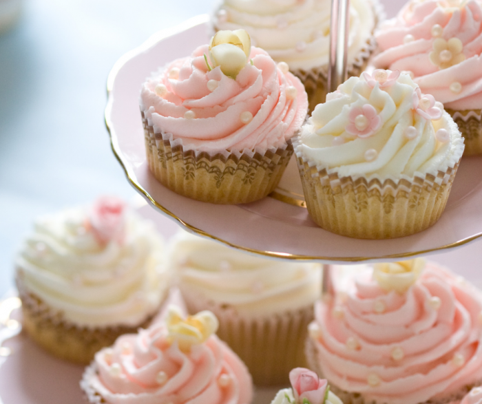 Pink and white cupcakes on a three tired pink tray